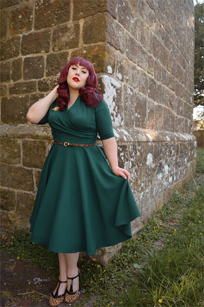 Plus size pinup Miss Amy May modelling the forest green Leyla midi swing dress by The Pretty Dress company for a fit and sizing review